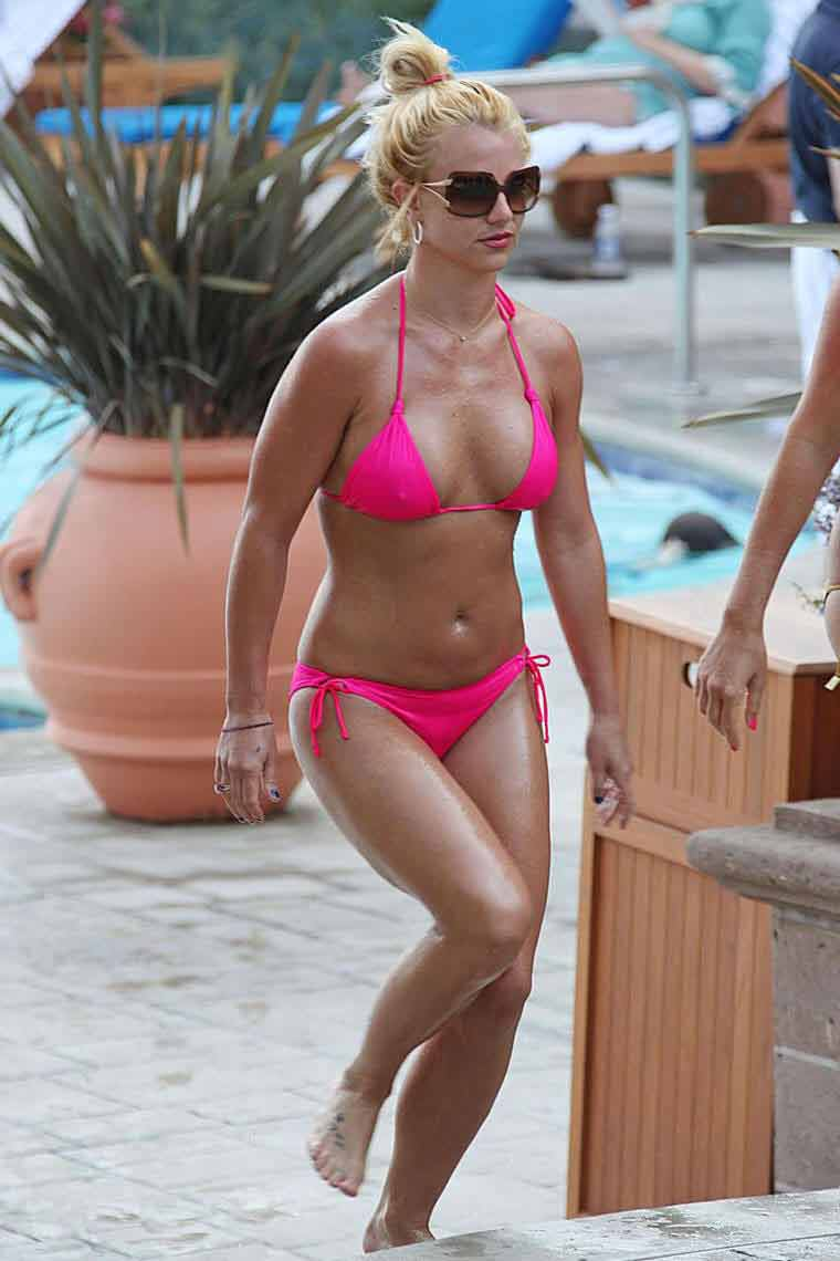 Britney Spears relaxes by the pool at the Ritz Carlton in a skimpy neon pink bikini her nipples are visible in bikini