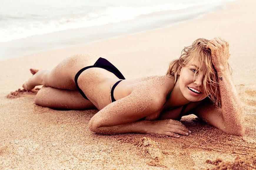 lara-bingle-swimwear-pictures-lying-on-beach-sand-sexy-looking-images