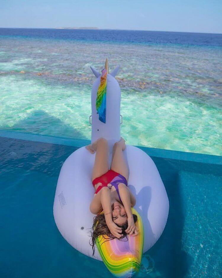 Mouni-Roy-enjoying-in-pool-on-pool-toy-in-red-blue-monokini-swimsuit